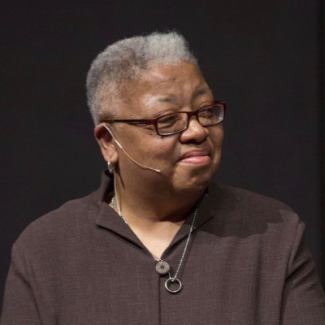 Gloria, wearing a microphone and brown shirt on, looking to the right