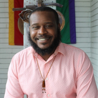 Jerron smiling wearing a necklace and pink-printed shirt