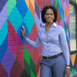 Latisha Johnson smiling against a colorful wall with a blue button-up shirt