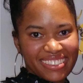 Mikaela smiling with hoop earrings on